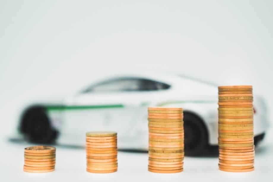 E-Auto und Münzen als Symbol für Betriebskosten